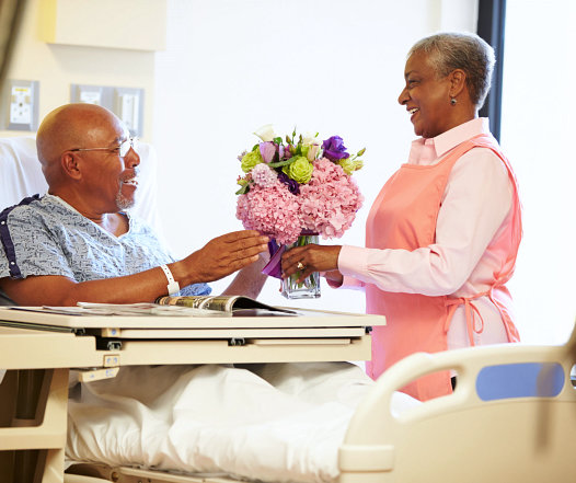 caretaker is bringing some flowers for her patient